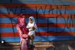 In this Sept. 27, 2019, photo, a Kashmiri woman protestor Jawahira Banoo carries her 3-year-old daughter Rutba and stands for a photograph outside a closed shop with a spray-painted graffiti after a protest on the outskirts of Srinagar, Indian controlled Kashmir. Banoo says she does not miss an opportunity to come out to the streets to protest. The men are at a higher risk of being detained, she says. (AP Photo/ Dar Yasin)