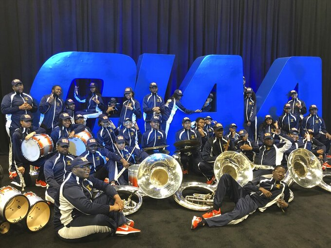 Members of the Virginia Union band pose in front of a CIAA Tournament sign in Charlotte, N.C., Friday, Feb. 28, 2020. The CIAA college basketball tournament is celebrating its 75th year. (AP Photo/Steve Reed)
