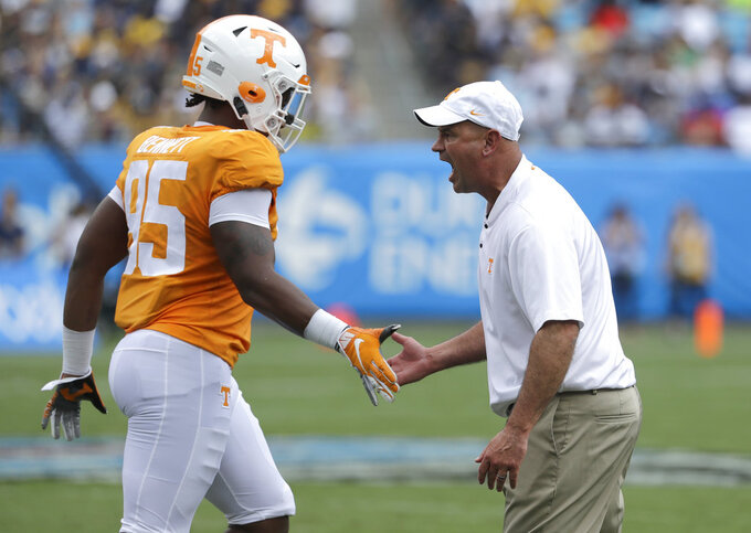 Tennessee head coach Jeremy Pruitt, right, greets Kivon Bennett (95) before an NCAA college football game against West Virginia in Charlotte, N.C., Saturday, Sept. 1, 2018. Tennessee believes it can play much better than it showed in a 40-14 season-opening loss to West Virginia. The Volunteers are hoping the lessons learned in that humbling defeat to open Jeremy Pruitt's coaching tenure can pay dividends the rest of the season. (AP Photo/Chuck Burton)
