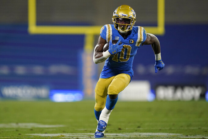 CORRECTS TO UCLA RUNNING BACK DEMETRIC FELTON NOT SOUTHERN CALIFORNIA QUARTERBACK MO HASAN - UCLA running back Demetric Felton runs to the end zone for a touchdown during the second quarter of an NCAA college football game against Southern California, Saturday, Dec 12, 2020, in Pasadena, Calif. (AP Photo/Ashley Landis)