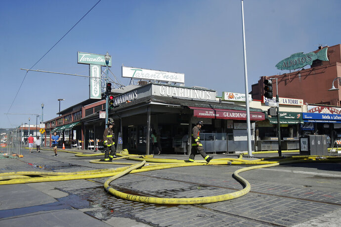 Firefighters step over hoses after a fire broke out before dawn at Fisherman's Wharf in San Francisco, Saturday, May 23, 2020. A warehouse was destroyed. Fire officials said no injuries have been reported Saturday morning and firefighters are making multiple searches to ensure no one was inside the building on Pier 45. (AP Photo/Jeff Chiu)