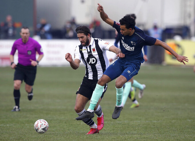 Chorley's Harry Cardwell, left, in action against Derby County's Harrison Solomon during the English FA Cup third round match at Victory Park in Chorley, England, Saturday Jan. 9, 2021. (Martin Rickett/PA via AP)