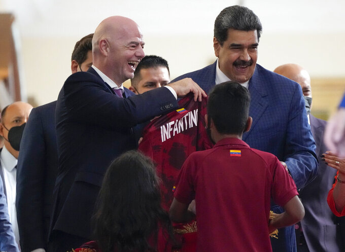 FIFA president Gianni Infantino, left, smiles after receiving the shirt of the Venezuelan soccer team with Venezuela President Nicolás Maduro, right, during his visit at Miraflores Presidential Palace in in Caracas, Venezuela , Friday , Oct 15, 2021. (AP Photo/Ariana Cubillos)