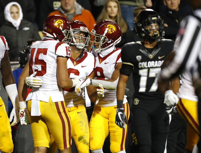 Southern California wide receiver Michael Pittman Jr., second from left, is congratulated by wide receivers Drake London, left, and Amon-Ra St. Brown after his go-ahead touchdown, as Colorado cornerback K.J. Trujillo walks away during the second half of an NCAA college football game Friday, Oct. 25, 2019, in Boulder, Colo. Southern California won 35-31. (AP Photo/David Zalubowski)