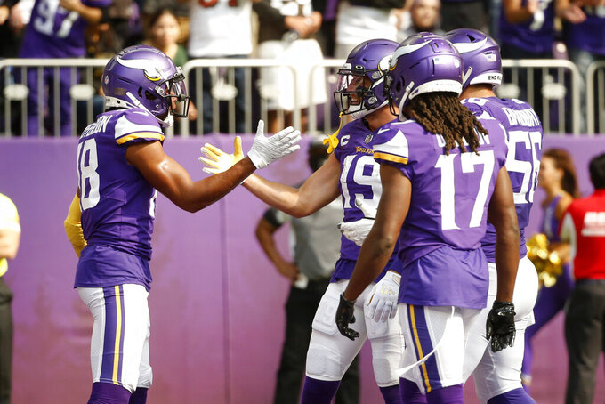 Minnesota Vikings wide receiver Justin Jefferson (18) celebrates with teammates after catching a 12-yard touchdown pass during the first half of an NFL football game against the Cleveland Browns, Sunday, Oct. 3, 2021, in Minneapolis. (AP Photo/Bruce Kluckhohn)