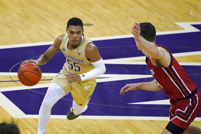 Washington guard Quade Green (55) drives around Utah guard Pelle Larsson, right, during the first half of an NCAA college basketball game, Sunday, Jan. 24, 2021, in Seattle. (AP Photo/Ted S. Warren)