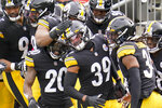 Pittsburgh Steelers free safety Minkah Fitzpatrick (39) is greeted by teammates in the end zone after intercepting a pass buy Cleveland Browns quarterback Baker Mayfield (6) and taking it in for a touchdown during the first half of an NFL football game, Sunday, Oct. 18, 2020, in Pittsburgh. (AP Photo/Gene J. Puskar)