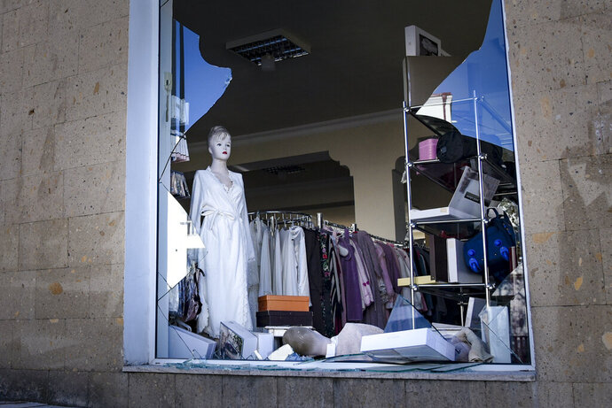 A view of a window of a clothing store, hit by shelling, during a military conflict in Stepanakert in the separatist region of Nagorno-Karabakh, Saturday, Oct. 17, 2020. Stepanakert, the regional capital of Nagorno-Karabakh, came under intense shelling overnight, leaving three civilians wounded, according to separatist authorities. (David Ghahramanyan, NKR InfoCenter/PAN Photo via AP)