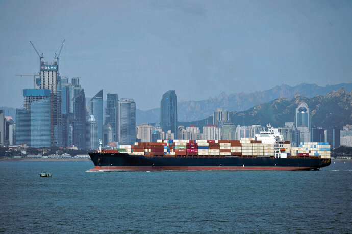 FILE -  In this Sept. 13, 2018, file photo, a container ship sails by the business district in Qingdao in east China's Shandong province. U.S.-Chinese trade contracted again in October, despite optimism about possible progress in talks aimed at ending a tariff war that threatens global economic growth. Chinese imports of U.S. goods fell 14.3% from a year earlier to $9.4 billion, customs data showed Friday, Nov. 8, 2019. (Chinatopix via AP, File)