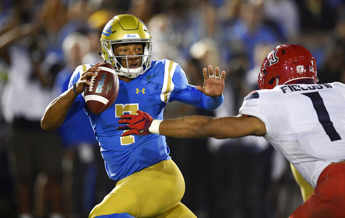 UCLA quarterback Dorian Thompson-Robinson, left, escapes a tackle by Arizona linebacker Tony Fields II as he tries to pass during the first half of an NCAA college football game, Saturday, Oct. 20, 2018, in Pasadena, Calif. (AP Photo/Mark J. Terrill)