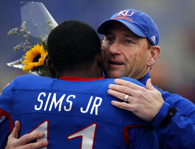 Kansas head coach David Beaty, right, embraces senior Steven Sims Jr. (11) before an NCAA college football game against Texas in Lawrence, Kan., Friday, Nov. 23, 2018. (AP Photo/Orlin Wagner)