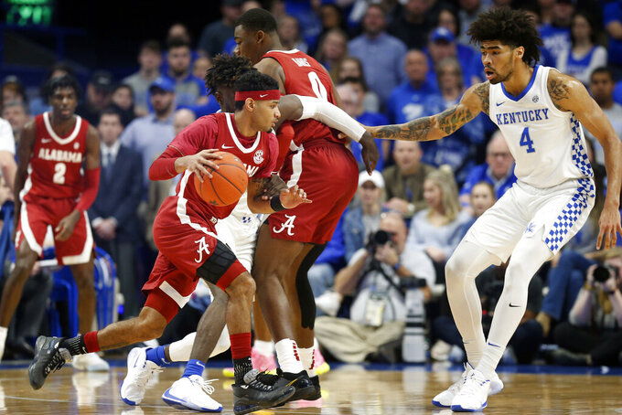 Alabama's James Bolden, left, looks for an opening on Kentucky's Nick Richards (4) during the first half of an NCAA college basketball game in Lexington, Ky., Saturday, Jan 11, 2020. (AP Photo/James Crisp)