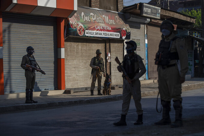 Paramilitary soldiers stands guard at an temporary check point on the first anniversary of India's decision to revoke the disputed region's semi-autonomy, in Srinagar, Indian controlled Kashmir, Wednesday, Aug. 5, 2020. Last year on Aug. 5, India's Hindu-nationalist-led government of Prime Minister Narendra Modi stripped Jammu-Kashmir of its statehood and divided it into two federally governed territories. Late Tuesday, authorities lifted a curfew in Srinagar but said restrictions on public movement, transport and commercial activities would continue because of the coronavirus pandemic. (AP Photo/ Dar Yasin)