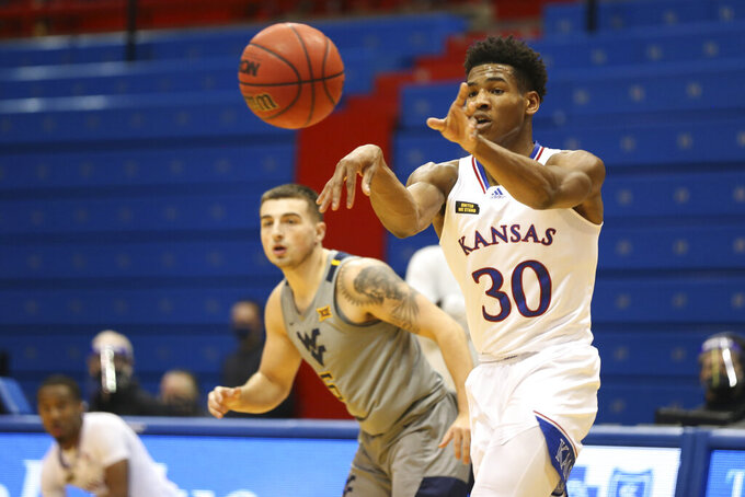 Kansas guard Ochai Agbaji passes to a teammate during the second half of the team's NCAA college basketball game against West Virginia on Tuesday, Dec. 22, 2020, in Lawrence, Kan. (Evert Nelson/The Topeka Capital-Journal via AP)