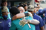 Seattle Mariners' Jarred Kelenic, center right, is embraced by Kyle Lewis (1) after hitting a two-run home run against the Cleveland Indians in the third inning of a baseball game Friday, May 14, 2021, in Seattle. (AP Photo/Elaine Thompson)
