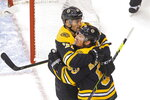 Boston Bruins' Brad Marchand (63) celebrates his goal against the Carolina Hurricanes with teammate Patrice Bergeron (37) during the second period of an NHL Eastern Conference Stanley Cup hockey playoff game in Toronto, Thursday, Aug. 13, 2020. (Chris Young/The Canadian Press via AP)