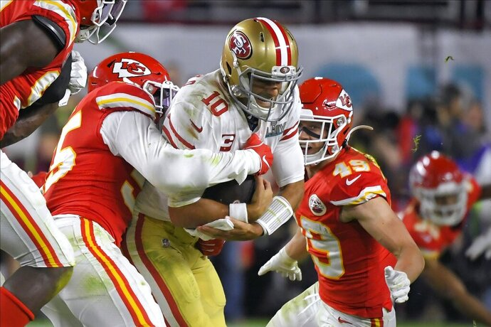 Kansas City Chiefs' Frank Clark, left, tries to tackle San Francisco 49ers' quarterback Jimmy Garoppolo during the second half of the NFL Super Bowl 54 football game Sunday, Feb. 2, 2020, in Miami Gardens, Fla. (AP Photo/Mark J. Terrill)