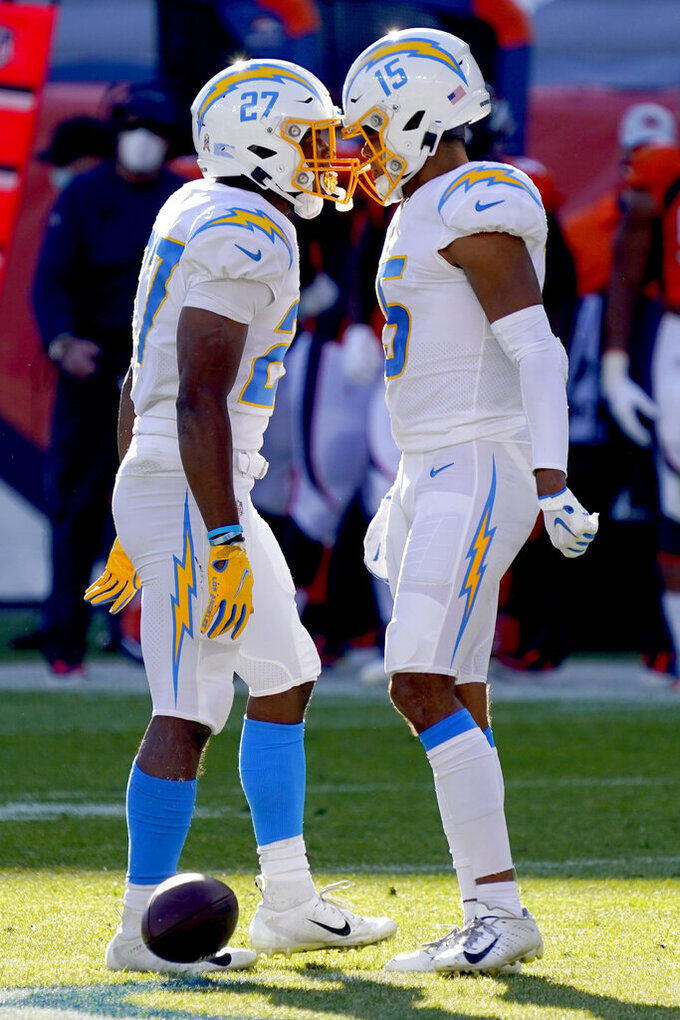 Los Angeles Chargers running back Joshua Kelley (27) celebrates a first down with wide receiver Jalen Guyton (15) during the first half of an NFL football game against the Denver Broncos, Sunday, Nov. 1, 2020, in Denver. (AP Photo/David Zalubowski)