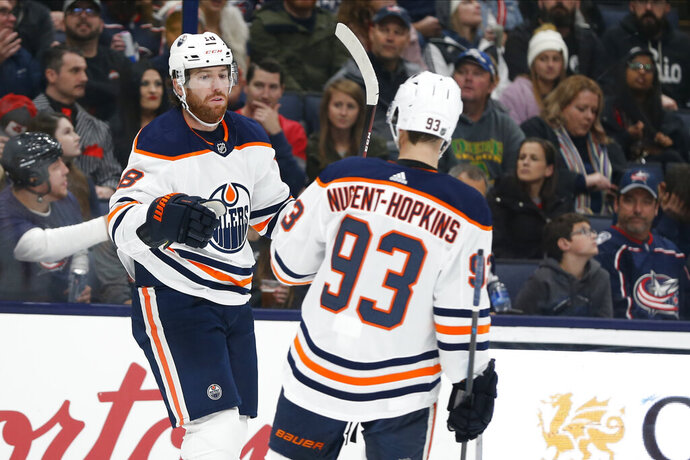 Edmonton Oilers' James Neal, left, celebrates his goal against the Columbus Blue Jackets with teammate Ryan Nugent-Hopkins during the first period of an NHL hockey game Wednesday, Oct. 30, 2019, in Columbus, Ohio. (AP Photo/Jay LaPrete)