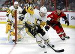 Pittsburgh Penguins defenseman Olli Maatta (3) tries to clear the puck as Ottawa Senators left wing Brady Tkachuk (7) pursues during second-period NHL hockey game action in Ottawa, Ontario, Saturday, Nov. 17, 2018. (Fred Chartrand/The Canadian Press via AP)