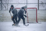 Brothers Joe, left, and Sam Lane, took each other on in a game of hockey during the snowy downpour at the Marie Park ice arena, Friday, Jan. 17, 2020, in Mendota Heights, Minn. (Elizabeth Flores/Star Tribune via AP)