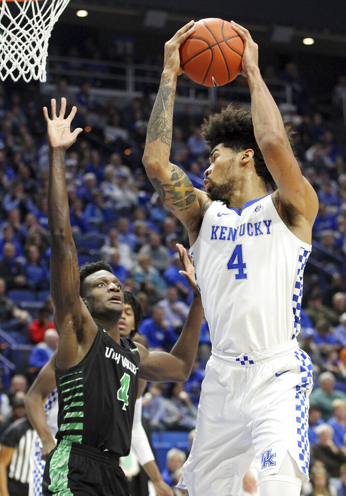 Kentucky's Nick Richards, right, pulls down a rebound near Utah Valley's Emmanuel Olojakpoke during the first half of an NCAA college basketball game in Lexington, Ky., Monday, Nov. 18, 2019. (AP Photo/James Crisp)