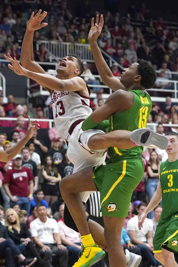 Stanford forward Oscar da Silva (13) drives to the basket against Oregon forward Chandler Lawson (13) during the second half of an NCAA college basketball game Saturday, Feb. 1, 2020, in Stanford, Calif. Stanford won 70-60. (AP Photo/Tony Avelar)