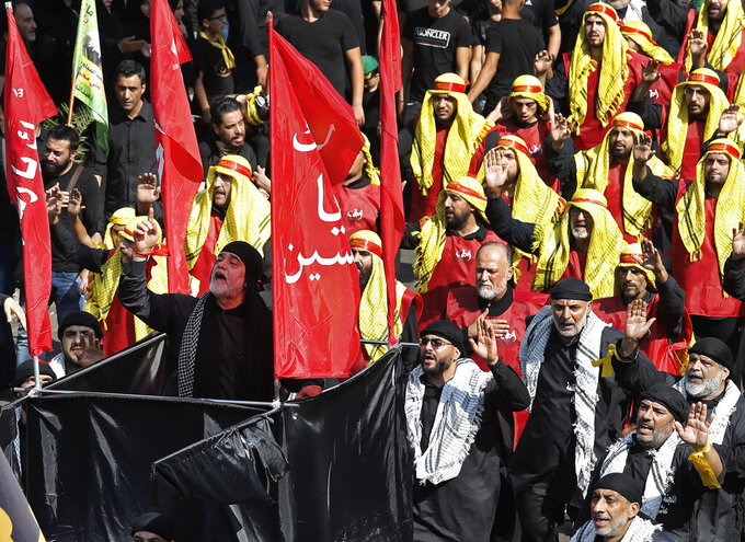 FILE - In this Sept. 10, 2019, file photo, Lebanese Shiite supporters of the Iranian-backed Hezbollah group raise their fists and chant slogans during Ashoura, the Shiite Muslim commemoration marking the death of Hussein, the grandson of the Prophet Muhammad, in present-day Iraq in the seventh century, Tuesday, Sept. 10, 2019, in Beirut, Lebanon. Shiites mark Ashoura, the 10th day of the month of Muharram, to commemorate the Battle of Karbala when Imam Hussein, a grandson of Prophet Muhammad, was killed. (AP Photo/Hussein Malla, File)