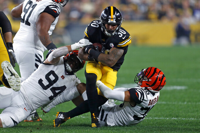 Pittsburgh Steelers running back James Conner (30) is tackled by Cincinnati Bengals defensive end Sam Hubbard (94) and free safety Jessie Bates (30) during the first half of an NFL football game in Pittsburgh, Monday, Sept. 30, 2019. (AP Photo/Tom Puskar)