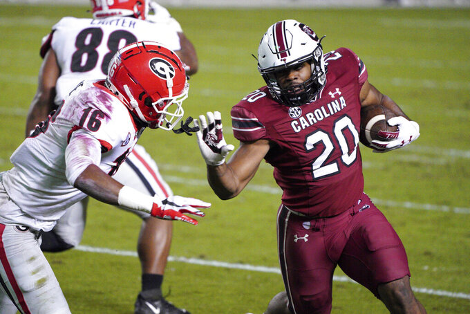 South Carolina running back Kevin Harris (20) carries the ball next to Georgia defensive back Lewis Cine (16) during the first half of an NCAA college football game Saturday, Nov. 28, 2020, in Columbia, S.C. (AP Photo/Sean Rayford)
