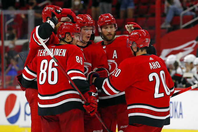 Carolina Hurricanes' Andrei Svechnikov, center, is congratulated on his goal by teammates during the second period of an NHL hockey game against the Chicago Blackhawks in Raleigh, N.C., Tuesday, May 4, 2021. (AP Photo/Karl B DeBlaker)