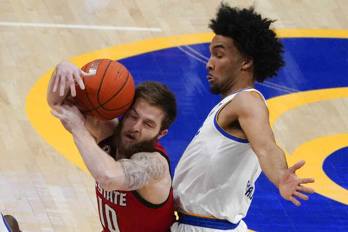 North Carolina State's Braxton Beverly, left, tries tp control the ball as Pittsburgh's Justin Champagnie defends during the first half of an NCAA college basketball game, Wednesday, Feb. 17, 2021, in Pittsburgh. (AP Photo/Keith Srakocic)