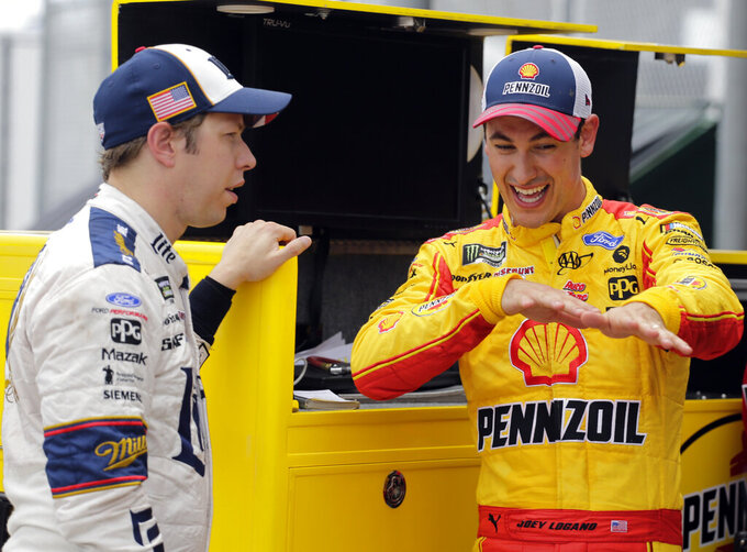 Joey Logano, right, talks with Brad Keselowski outside their garages during a NASCAR auto race practice at Daytona International Speedway, Thursday, July 4, 2019, in Daytona Beach, Fla. (AP Photo/Terry Renna)