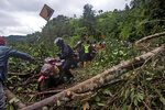 Motorists make their way through a road affected by an earthquake-triggered landslide near Mamuju, West Sulawesi, Indonesia, Saturday, Jan. 16, 2021. Damaged roads and bridges, power blackouts and lack of heavy equipment on Saturday hampered Indonesia's rescuers after a strong and shallow earthquake left a number of people dead and injured on Sulawesi island. (AP Photo/Yusuf Wahil)