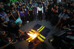 Women burn an America soccer club flag during a performance of the
