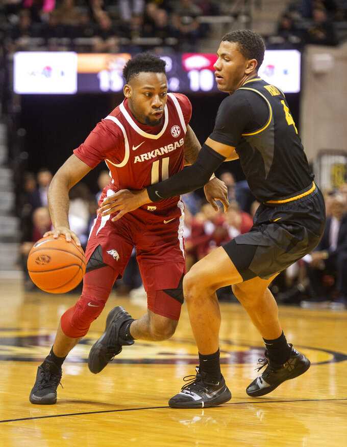 Arkansas's Keyshawn Embery-Simpson, left, dribbles past Missouri's Javon Pickett, right, during the first half of an NCAA college basketball game Tuesday, Feb. 12, 2019, in Columbia, Mo. (AP Photo/L.G. Patterson)
