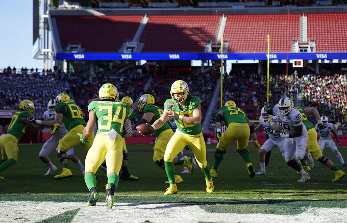 Oregon quarterback Justin Herbert (10) hands off to running back CJ Verdell (34) against Michigan State during the second half of the Redbox Bowl NCAA college football game Monday, Dec. 31, 2018, in Santa Clara, Calif. (AP Photo/Tony Avelar)