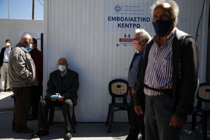 Local residents wearing face masks to help curb the spread of the coronavirus, wait outside a vaccination center on the Aegean island of Naxos, Greece, Tuesday, May 11, 2021. A vaccination program for Greek islands is being accelerated to cover all local residents by the end of June, the government has announced ahead of the launch of the tourism season. (AP Photo/Thanassis Stavrakis)
