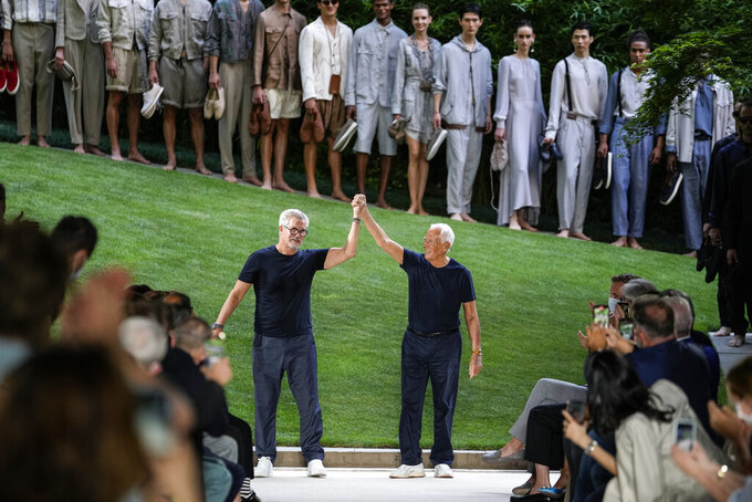 Giorgio Armani, right, and Leo Dell'Orco accept applause at the conclusion of the Giorgio Armani men's Spring Summer 2022 collection, in Milan, Italy, Monday, June 21, 2021. (AP Photo/Luca Bruno)