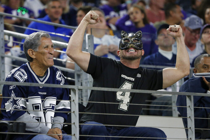 A Dallas Cowboys fan wears a black cat mask as he cheers on the team during the second half of an NFL football game against the Minnesota Vikings in Arlington, Texas, Sunday, Nov. 10, 2019. (AP Photo/Michael Ainsworth)