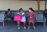 Two women wearing face masks to protect against the spread of the new coronavirus, sit on a bench at the port of Piraeus, near Athens, Sunday, Aug. 30, 2020 Greek health officials said Friday that they are expanding for another two weeks a series of domestic health measures, including the obligatory use of masks in most indoors public areas, distancing on beaches and a ban on large gatherings on the occasion of religious festivals. (AP Photo/Michael Varaklas)