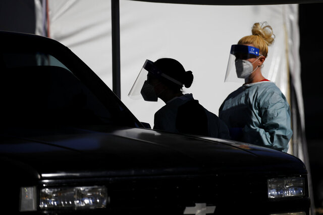 Healthcare workers test patients in their cars at a drive-thru coronavirus testing site run by the University of Nevada Las Vegas School of Medicine and the Nevada National Guard, Friday, July 10, 2020, in Las Vegas. (AP Photo/John Locher)