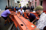 Protesters remove street barricades that are filled with water as police block them from reaching La Fortaleza governor's residence in San Juan, Puerto Rico, Sunday, July 14, 2019. Protesters are demanding Gov. Ricardo Rosselló step down for his involvement in a private chat in which he used profanities to describe an ex-New York City councilwoman and a federal control board overseeing the island's finance. (AP Photo/Carlos Giusti)