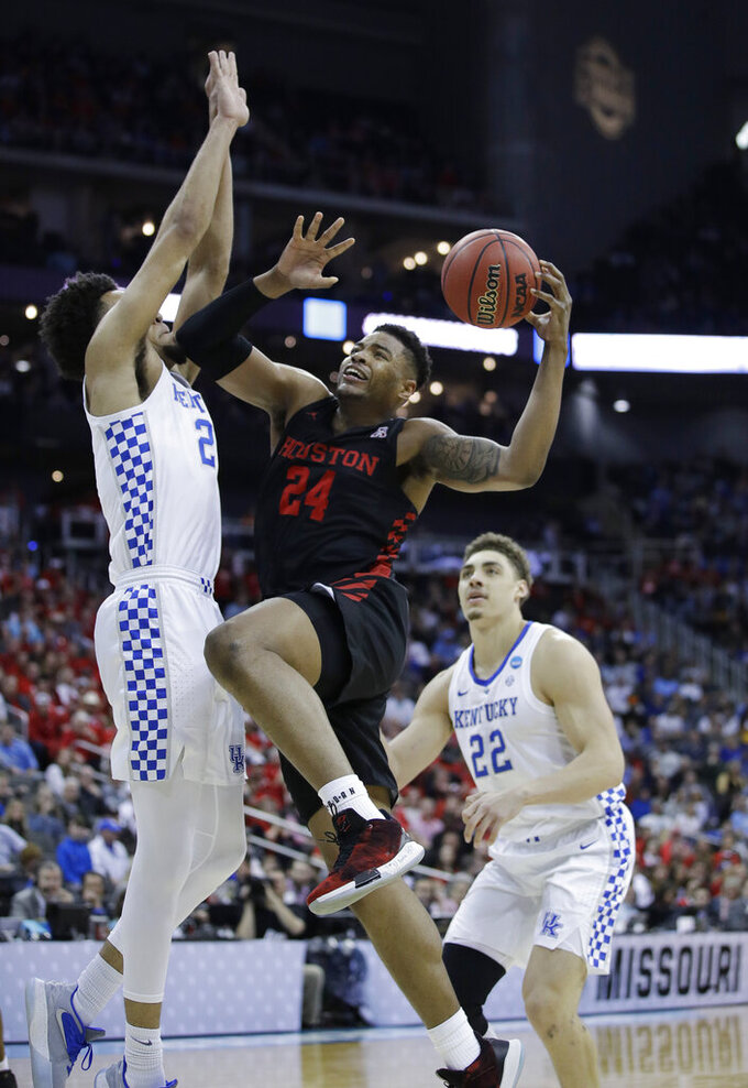 Houston's Breaon Brady (24) heads to the basket past Kentucky's EJ Montgomery and Kentucky's Reid Travis (22) during the first half of a men's NCAA tournament college basketball Midwest Regional semifinal game Friday, March 29, 2019, in Kansas City, Mo. (AP Photo/Charlie Riedel)