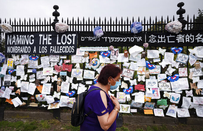 FILE - In this May 28, 2020, file photo, a woman passes a fence outside Brooklyn's Green-Wood Cemetery adorned with tributes to victims of COVID-19 in New York. The U.S. death toll from the coronavirus topped 200,000 Tuesday, Sept. 22, a figure unimaginable eight months ago when the scourge first reached the world's richest nation with its sparkling laboratories, top-flight scientists and towering stockpiles of medicines and emergency supplies. (AP Photo/Mark Lennihan, File)