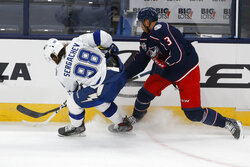 Tampa Bay Lightning's Mikhail Sergachev, left, of Russia, and Columbus Blue Jackets' Seth Jones fight for a loose puck during the third period of an NHL hockey game Saturday, Jan. 23, 2021, in Columbus, Ohio. The Blue Jackets beat the Lightning 5-2. (AP Photo/Jay LaPrete)