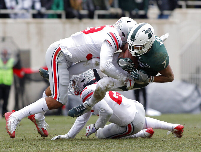 Michigan State receiver Cody White, right, is stopped by Ohio State's Malik Harrison during the first quarter of an NCAA college football game, Saturday, Nov. 10, 2018, in East Lansing, Mich. (AP Photo/Al Goldis)