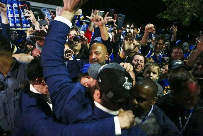 Fans cheer for members of the St. Louis Blues NHL hockey team, foreground, after their arrival at the airport in St. Louis early Thursday, June 13, 2019. The Blues defeated the Boston Bruins 4-1 in Game 7 of the Stanley Cup finals to win their first NHL championship Wednesday night in Boston. (Colter Peterson/St. Louis Post-Dispatch via AP)