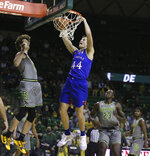 Kansas forward Mitch Lightfoot, right, dunks over Baylor guard Matthew Mayer in the first half of an NCAA college basketball game, Monday, Jan. 18, 2021, in Waco, Texas. (Rod Aydelotte/Waco Tribune-Herald via AP)