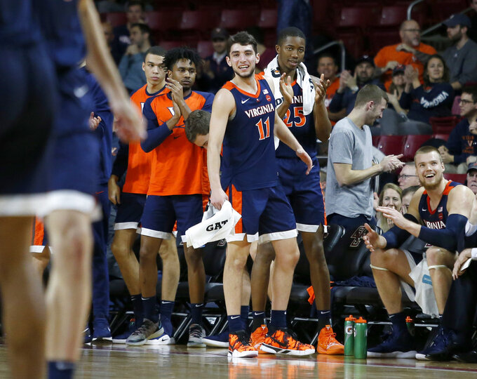 Virginia players, including Ty Jerome and Mamadi Diakite, cheer their team from the bench during the second half of an NCAA basketball game against Boston College, Wednesday, Jan. 9, 2019, in Boston. (AP Photo/Mary Schwalm)
